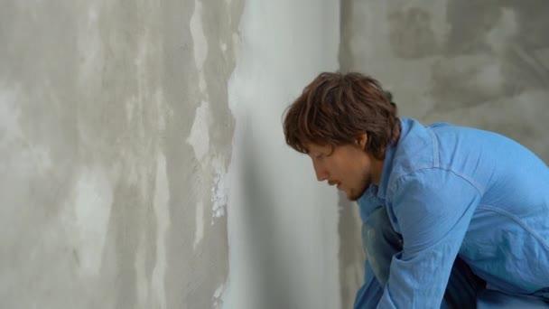 Zeitlupenaufnahme eines jungen Malers, der Kitt auf die Wände aufträgt