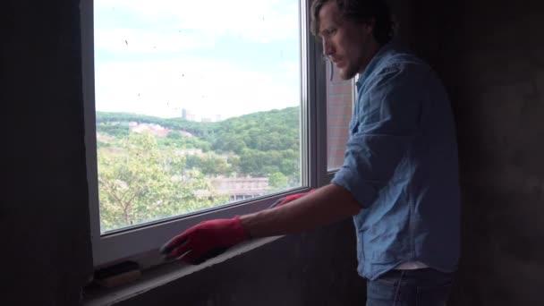 mladý muž v instalaci parapetu uvnitř rukavice