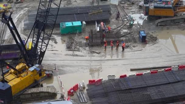 Továrních dělníků a strojů, které pracují na budování staveniště