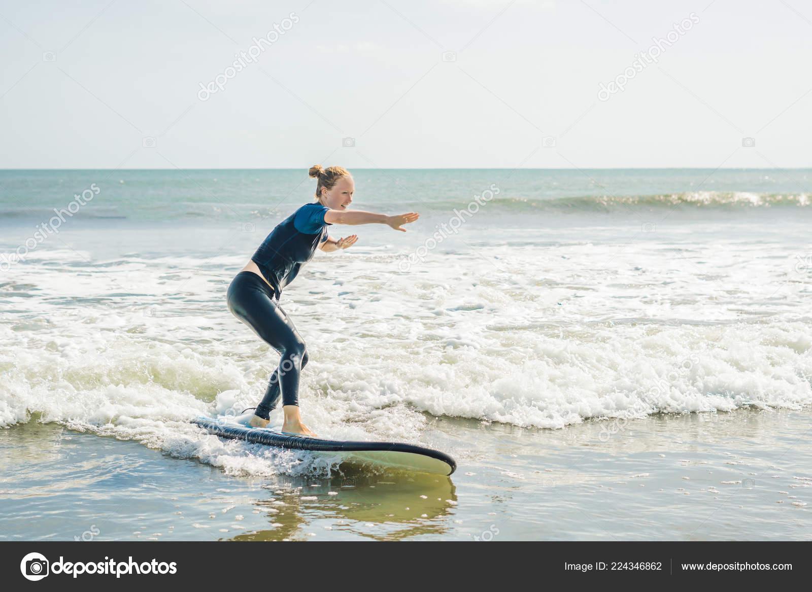 Joyeuse Jeune Femme Surfant Avec Planche Surf Bleu Novice Sur Photographie Galitskaya C 224346862