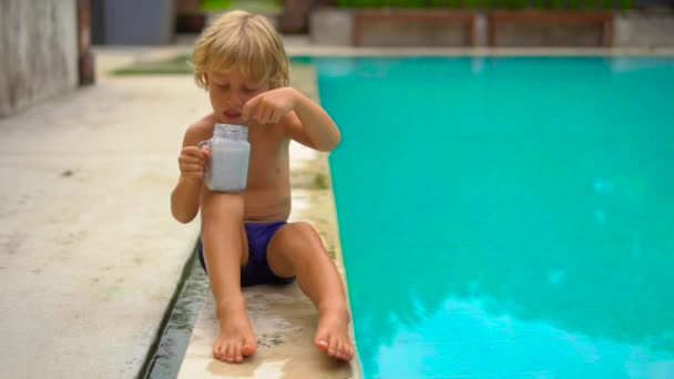 Slowmotion shot of the little boy eats a chia pudding sitting on a side of a pool