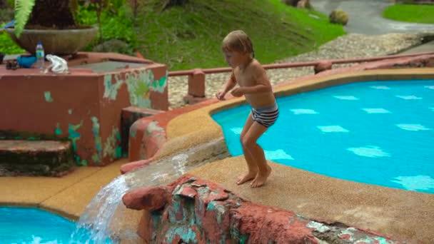 Superzeitlupenaufnahme eines kleinen Jungen, der in ein Wasserbecken springt