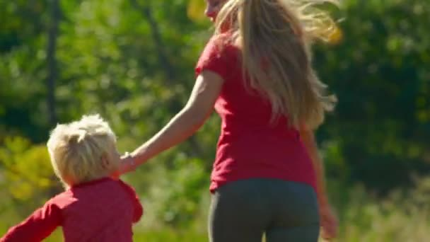 Slow motion shot of a young woman and her little son have fun on a lawn