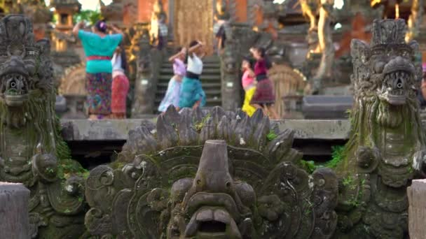 Saraswati Temple in Ubud village on the Bali island, Indonesia. Stone statues inside the temple with blurred a woman teacher which is teaching group of girls a traditional Balinese dance.