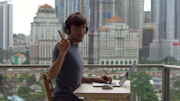 Fiatal férfi szabadúszó, hogy megtagadó gesztust, miközben dolgozik a laptop erkély is tartozik, a háttérben a város központjában.