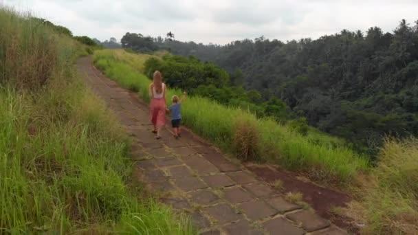 Luftaufnahme einer jungen Frau und ihres kleinen Sohnes auf dem Künstlerpfad - Campuhan-Gratwanderung im Ubud-Dorf auf der Bali-Insel.