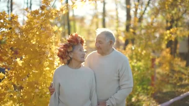Slowmotion shot of an elderly couple hugging and smiling to each other in a park in a beautiful autumn environment. Old woman wears a wreath of autumn leaves