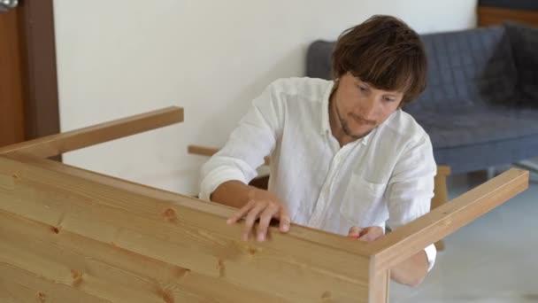 Mladý muž profesionální nábytek assembler sestavuje dřevěný stůl v kuchyni