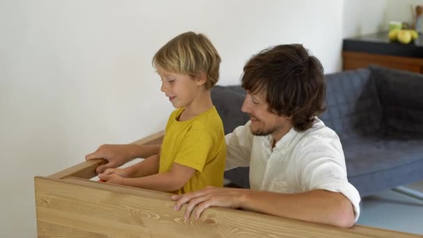 Father and son assemble wooden furniture from small parts. Little boy helps his father to assemble a table.