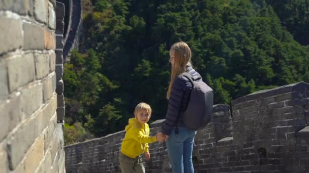 Slowmotion shot of a happy young woman and her little son standing on the Chinese Great wall