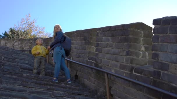 Slowmotion shot of a happy young woman and her little son standing on stairs of the Chinese Great wall