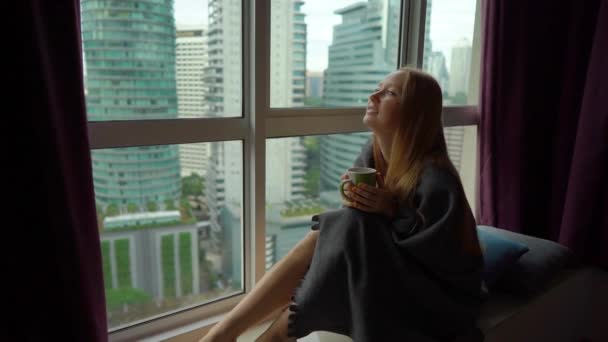 Super Slow Motion shot of a young woman that drinks tea or coffee wrapped in a plaid sitting by a panoramic window in downtown of a city with skyscrapers at a background