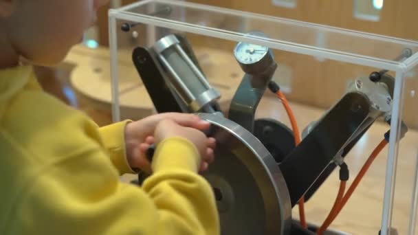 Little boy visits a science museum for children. He compresses air with a hand pump in order to make a plastic bottle fly up