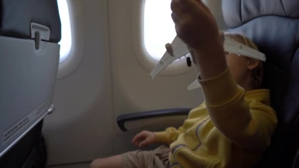 Slowmotion shot of a little boy that plays with white toy airplane sitting in a chair onboard of an airplane. Freedom concept. Childhood concept. Children travel concept
