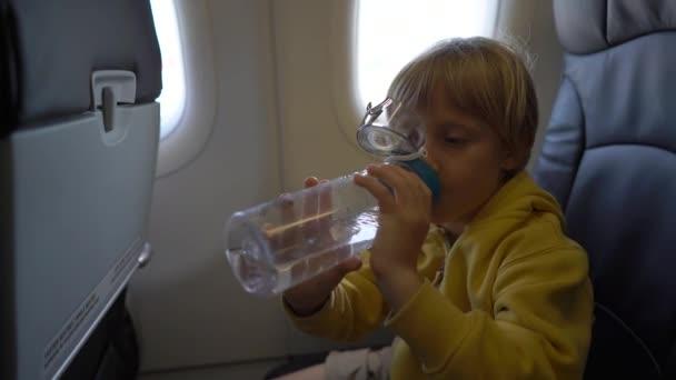 Slowmotion lövés egy kisfiú, hogy iszik víz, ül egy széken egy repülőgép fedélzeti újrahasznosítható műanyag palackból. Gyermekek utazási koncepció. Szennyezés csökkentésére a műanyag fogalom. Egyszer használatos