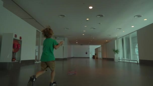 Slowmotion shot of a little boy that run through airport holding white toy airplane in his hand. Freedom concept. Childhood concept. Children travel concept