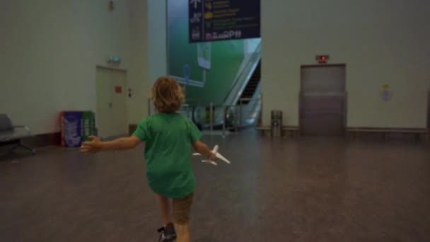 KUALA LUMPUR, MALAYSIA - NOVEMBER 20, 2018: Slowmotion shot of a little boy that run through airport holding white toy airplane in his hand. Freedom concept. Childhood concept. Children travel concept