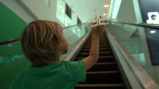 Slowmotion shot of a little boy moves up the escalator holding white toy airplane in his hand. Freedom concept. Childhood concept. Children travel concept