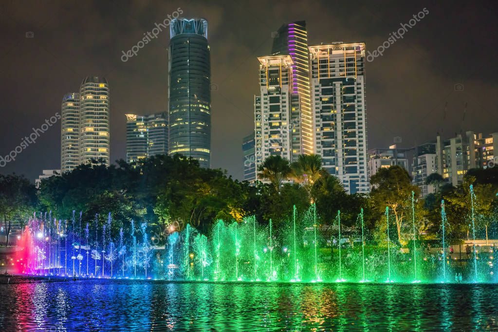 The colorful fountain on the lake at night, near by Twin Towers with city on background. Kuala Lumpur, Malaysia