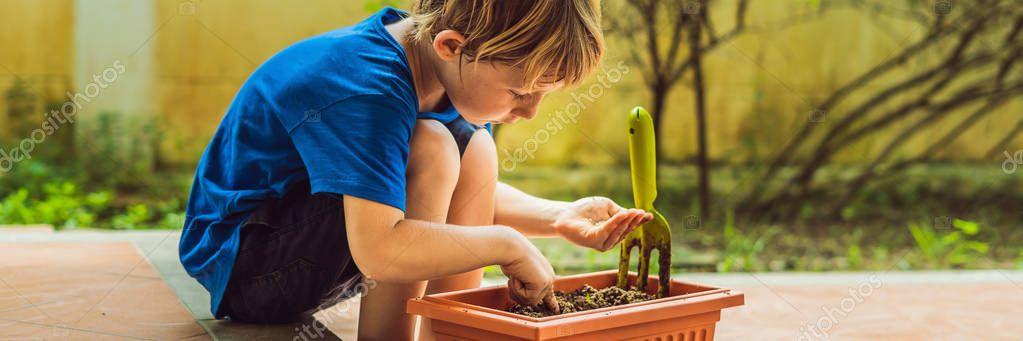 Little cute boy sows seeds in a flower pot in the garden BANNER, LONG FORMAT