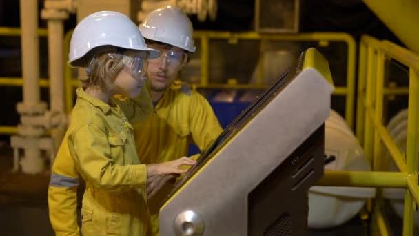 Ein junger Mann und ein kleiner Junge stehen beide in gelber Arbeitsuniform, Brille und Helm in einem Industrieumfeld, einer Ölplattform oder einer Flüssiggasanlage und schauen auf einen Bildschirm. Zeitlupenschuss