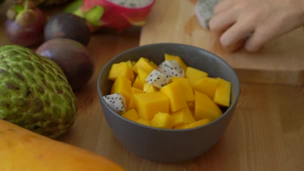 4x times Slowmotion shot of a young woman putting the dragon fruit cubes into a grey ceramic bowl and lots of tropical fruits lay on a table