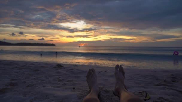 Slowmotion shot - legs of a man on a beach watching a fantastic sunset.