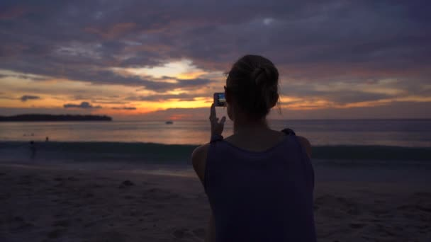 Slowmotion shot of a young woman on a beach watching a fantastic sunset