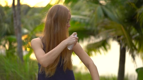 Superslowmotion shot of a beautiful young woman applying an antimosquito repellent spray on her skin. A tropical background. Mosquito defense concept
