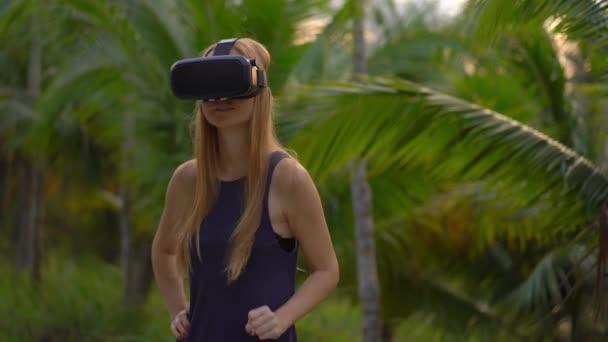 Detailní záběr krásné mladé ženy používají Vr headset v tropickém parku. Vr brýle člověk cítí, jako by byl v tropech. Rozšířená realita koncept