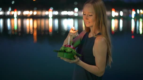 Slowmotion shot of a beautiful young woman that lights a candle holding a krathong in her hands celebrating a Loi Krathong holiday in Thailand