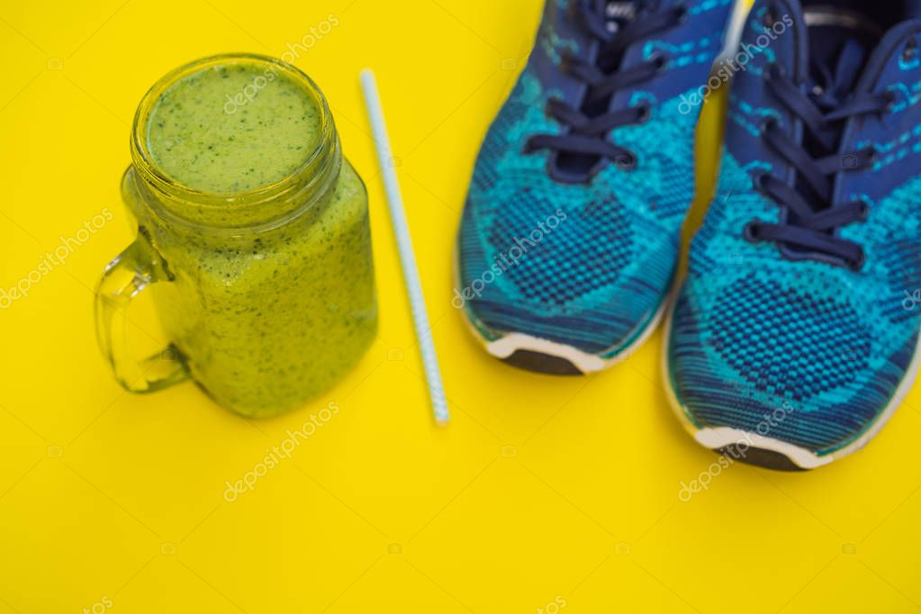 Everything for sports turquoise, blue shades on a yellow background and spinach smoothies. Yoga mat, sport shoes sportswear and bottle of water. Concept healthy lifestyle, sport and diet. Sport
