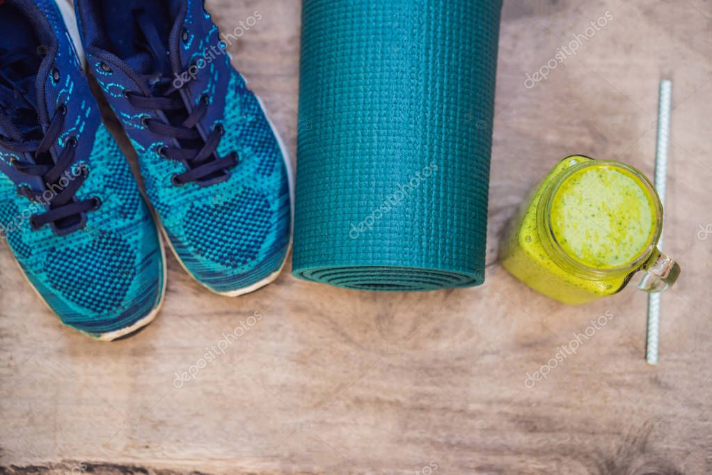 Everything for sports turquoise, blue shades on a wooden background and spinach smoothies. Yoga mat, sport shoes sportswear and bottle of water. Concept healthy lifestyle, sport and diet. Sport