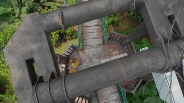 Vzdušný záběr malého chlapce, který běží na mostě přes džungle. Cestování v pojetí jihovýchodní Asie