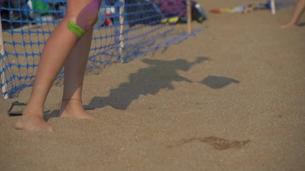 Legs of a woman and her body shadow playing volleyball on a beach