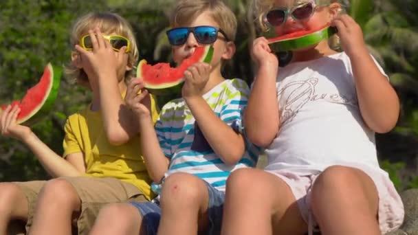 Csoport gyermekek étkezési görögdinnye ül egy trópusi tengerparton. Gyermekkori koncepció. Nyári koncepció