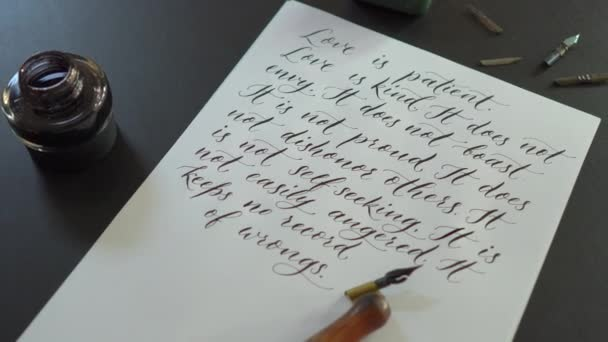 Closeup shot of a calligraphy tools and a bottle of ink laying around a sheet of a white paper with several lines from a Bible about love is written on it