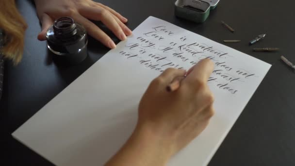 Close up shot of a young woman calligraphy writing on a paper using lettering technique. She writes a wedding vow Love is patient love is kind