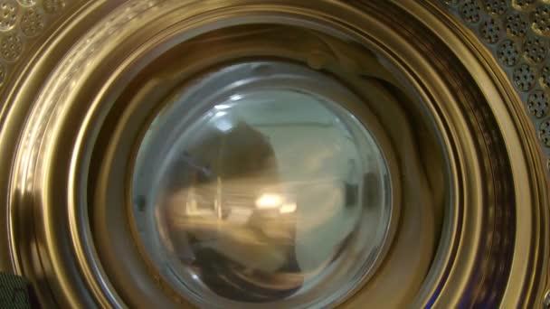 kilátás a mosógép, mint egy fiatal nő helyezi piszkos ruhákat bele