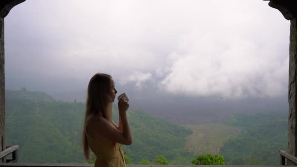 Slowmotion shot of a young woman drinking tea or coffee in a cafe in the mountains with a view on a mountain Batur and its caldera hidden in clouds. Travell to Bali concept