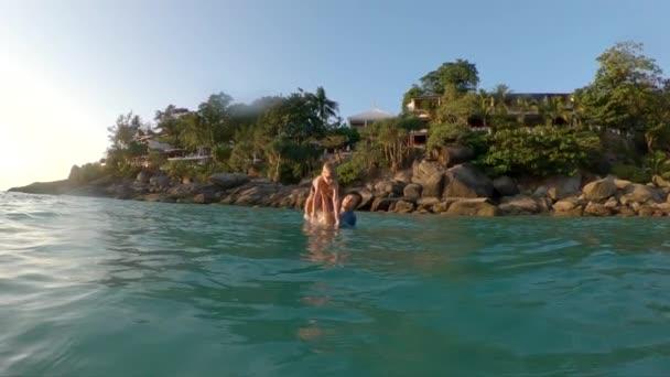 Superslowmotion lövés egy fiatal apa throuing a kis fiát a tengerbe. Nyári koncepció. Utazik-val Kids fogalom
