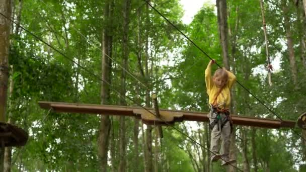 Ein kleiner Junge im Sicherheitsgurt klettert auf einer Route in Baumwipfeln in einem Wald-Erlebnispark. Er klettert auf einem Hochseilgarten. Outdoor-Vergnügungszentrum mit Kletteraktivitäten bestehend aus Seilrutschen und allen