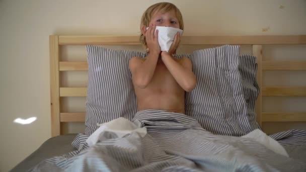Superzeitlupenaufnahme eines kranken kleinen Jungen im Bett. Grippekonzept