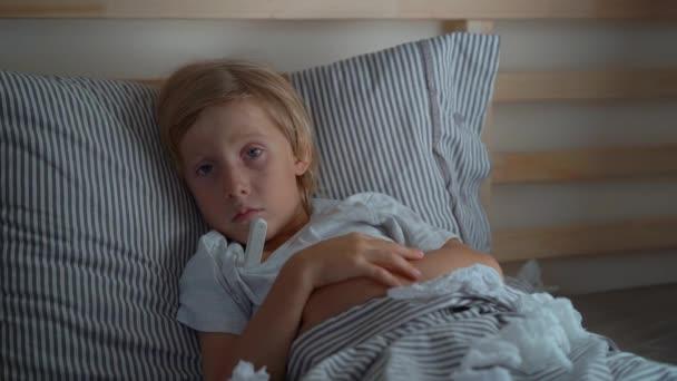 Superslowmotion Schuss eines kranken kleinen Jungen mit einem Thermometer in einem Bett. Baby-Grippe-Konzept