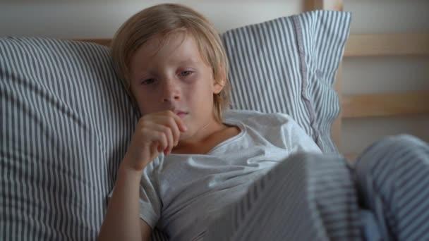 Kranker kleiner Junge in einem Bett. Junge hustet im Bett. Baby-Grippe-Konzept