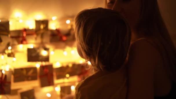 Slowmotion Nahaufnahme von einer Mutter und ihrem kleinen Sohn blick auf einen Adventskalender hängen deiner Bett beleuchtung mit Weihnachtsbeleuchtung. Vorbereitung auf Weihnachten und Neujahr Konzept. Adventskalender