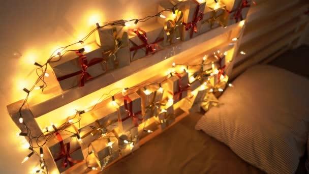 Slowmotion-Aufnahme eines Adventskalenders, der an einem Bett hängt, das mit Weihnachtsbeleuchtung aufgehellt ist. Vorbereitung auf Weihnachten und Neujahr Konzept. Adventskalenderkonzept