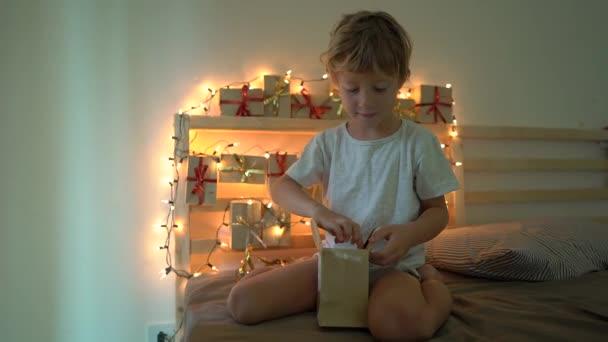 Zeitlupenaufnahme eines kleinen Jungen beim Öffnen eines Geschenks aus einem Adventskalender, das an einem mit Weihnachtslichtern beleuchteten Bett hängt. Wir bereiten uns auf Weihnachten und Neujahr vor. Advent