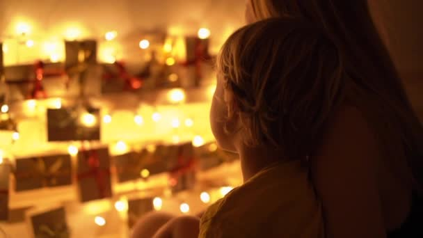 Slowmotion Closeup Shot Of A Mother And Her Little Son Look At An Advent Calendar Hanging On A Bed Lighten With Christmas Lights Getting Ready For Christmas And New Year Concept Advent Calendar