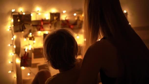 Zeitlupen-Nahaufnahme einer Mutter und ihres kleinen Sohnes beim Betrachten eines Adventskalenders, der an einem mit Weihnachtslichtern beleuchteten Bett hängt. Wir bereiten uns auf Weihnachten und Neujahr vor. Adventskalender